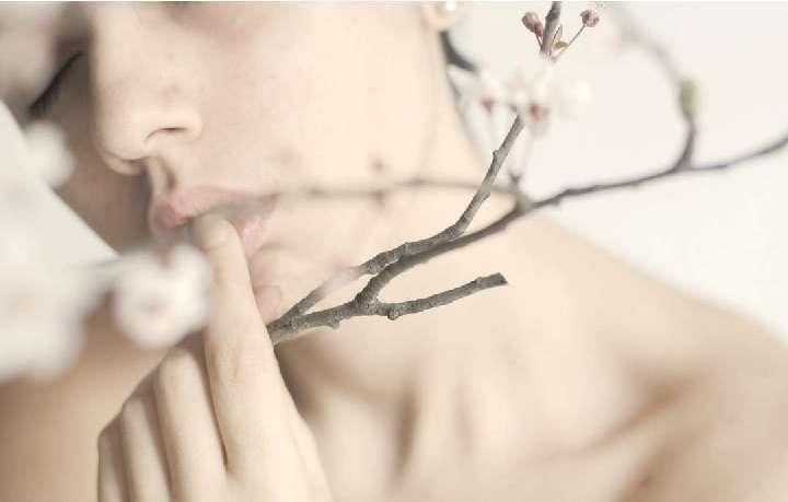 női arc és faág virággal
